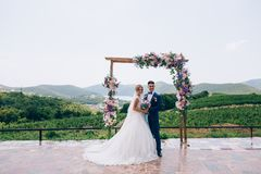 The newlyweds are posing in the open air near the flower arch and smiling broadly. Beautiful couple outdoors enjoying. The wedding day Stock Image