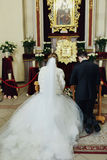 Newlyweds pray on kneels in the front of icon in the church Stock Photos