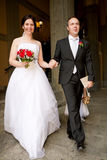 Newlyweds registry office. Newly wed couple : groom and bride walking out of the civil registry office royalty free stock photography