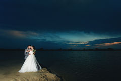 Newlyweds on the river bank at night Stock Images