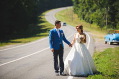 Newlyweds on Road. Newlyweds walking on road in forest Royalty Free Stock Image