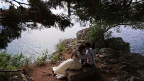 Newlyweds on the rocks near the sea. Territory of the park Miloc stock video footage