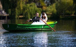 Newlyweds rowing in boat Royalty Free Stock Images