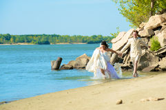 Newlyweds running on the beach Stock Images