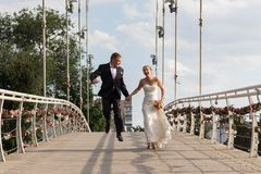Newlyweds running on the bridge Royalty Free Stock Photo