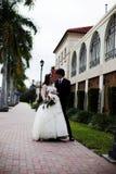 Newlyweds on sidewalk. A newlywed couple pause and pose on a sidewalk royalty free stock photo