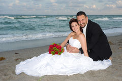 Newlyweds Sitting. Newlyweds Cuddling at the Beach Stock Photography