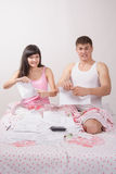 Newlyweds sitting in bed tearing account for rent Royalty Free Stock Images