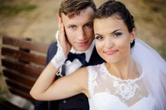 Newlyweds sitting at bench in park royalty free stock photography