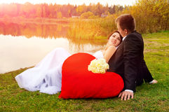 Newlyweds sitting on the grass Royalty Free Stock Images