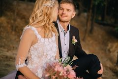 Newlyweds sitting on the lake and looking at each other royalty free stock photo