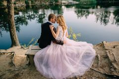 Newlyweds on the lake shore on a summer evening royalty free stock photo
