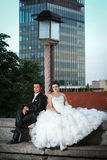 Newlyweds sitting next to street lamp Royalty Free Stock Photography
