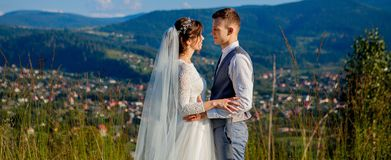 Newlyweds smile and hug each other among the meadow on top of the mountain. Wedding walk in the woods in the mountains, the gentle. Emotions of the couple royalty free stock image