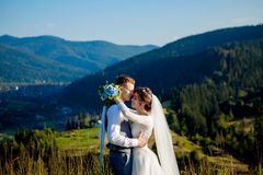 Newlyweds smile and hug each other among the meadow on top of the mountain. Wedding walk in the woods in the mountains, the gentle. Emotions of the couple royalty free stock photos