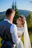 Newlyweds smile and hug each other among the meadow on top of the mountain. Wedding walk in the woods in the mountains, the gentle. Emotions of the couple stock photos
