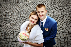 Newlyweds smiling, view from above, on a background of cobblesto Royalty Free Stock Photos