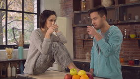 Newlyweds spend time in apartment. Wife and husband talking and drinking water in the kitchen. Happy family enjoy and have fun in the morning in flat stock video