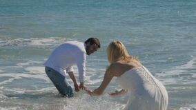 The newlyweds sprinkle water on each other. A charming couple is standing in the water and laughing. The girl in the wedding dress turns to the camera and goes stock video