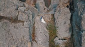 Newlyweds stand on a high slope of the mountain. Groom and bride. Arial view stock video footage