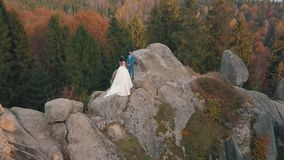 Newlyweds stand on a high slope of the mountain. Groom and bride. Arial view stock video