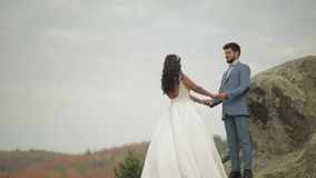 Newlyweds stand on a high slope of the mountain. Groom and bride stock footage