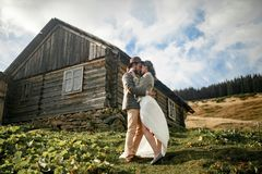Newlyweds stand and hug on background of old wooden hut in mount Stock Images