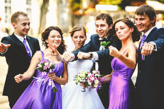 Newlyweds stand together with their friends during a walk around Royalty Free Stock Photography