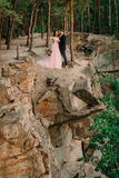 Newlyweds standing at the edge of the rock and couple looking each other with tenderness and love. Bride and groom Stock Photography