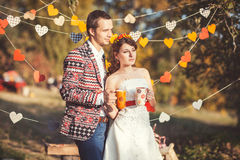 Newlyweds standing embracing in autumn park. And hold a cup with a drink in hands Stock Photos
