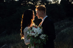 Newlyweds standing and hugging outdoors, close-up. Newlyweds are standing and hugging outdoors, backlight, low key Royalty Free Stock Image