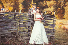 Newlyweds standing near the wicker fence. In autumn park, groom put his hands on the shoulders of the bride Stock Photo