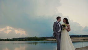 Newlyweds standing on the river bank stock video