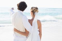 Newlyweds standing by the sea with husband pointing Royalty Free Stock Photography