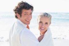 Newlyweds standing by the sea looking at the camera Stock Photo