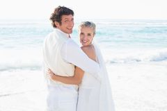 Newlyweds standing by the sea smiling at camera Royalty Free Stock Image