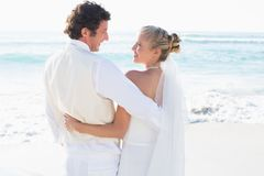 Newlyweds standing by the sea smiling at each other Stock Photos