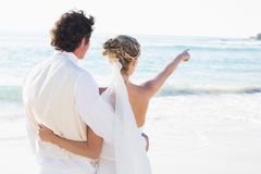 Newlyweds standing by the sea with wife pointing Royalty Free Stock Photos