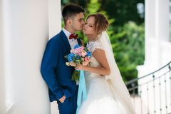 Newlyweds stroll in a green park with white columns. A man in a wedding suit wants to kiss a girl. A woman in a wedding royalty free stock photo