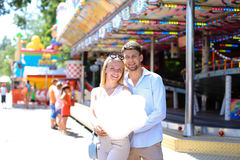 Newlyweds strolling in luna park, looking at each other, cuddlin Royalty Free Stock Photography