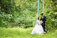 Newlyweds on a swing Royalty Free Stock Photography