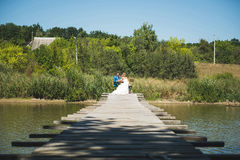 Newlyweds at Table on Bridge. Newlyweds sitting at table on bridge at sunny wedding day Stock Photo