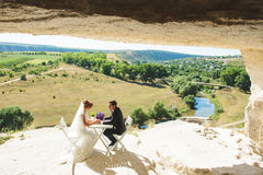 Newlyweds at Table in Cave. Newlyweds sitting at table in cave at sunny day Stock Images