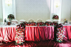 Newlyweds table covered with red cloth, decorated with roses and Royalty Free Stock Photos