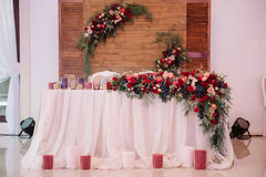 Newlyweds table, decorated with bouquet and candles. Newlyweds table, decorated with bouquet, consists of roses, grape and apples, and candles Royalty Free Stock Photos