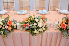 Newlyweds table decorated with bouquet and candles. In peachy colours with monogram Royalty Free Stock Image