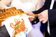 Newlyweds tear off a piece of wedding caravan. Russian tradition at the wedding Royalty Free Stock Image