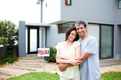 Newlyweds with their new house. Happy newlyweds with their new house royalty free stock image