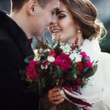 Newlyweds touch each other with noses, while bride holds a bouqu Royalty Free Stock Image