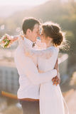 Newlyweds touch each other with noses, while bride holds  bouquet on cityscape background Stock Photo